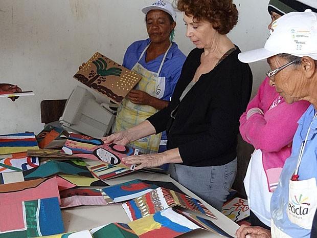 Artista plástica Lúcia Rosa (de preto) coordena projeto que ensina catadoras a produzir capas para os livros, escritos por autores da cidade (Foto: Gabriela Alcântara   G1)