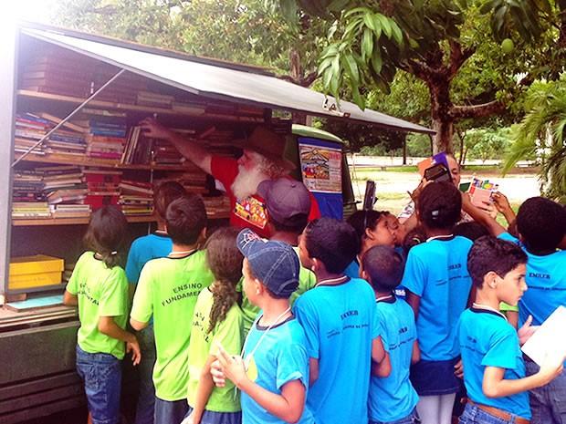 Crianças se aglomeram ao redor da biblioteca móvel por onde ela passa (Foto: Marcelo Ferraz/G1)