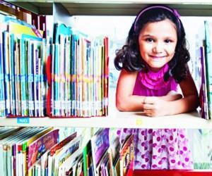 Ivy dos Santos Dias se diverte em uma biblioteca. Ela foi a vencedora do concurso Retratos da Educação em Família (Foto: Cintia Sanchez/Divulgação)