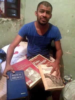 Cícero Pereira Batista mostra livros achados no lixo e com os quais estudou para virar médico (Foto: Raquel Morais/G1)