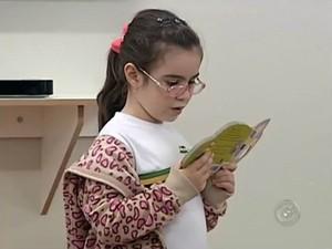 A estudante Gabriela Santos, de 6 anos, concentrada na leitura (Foto: Reprodução / TV TEM)