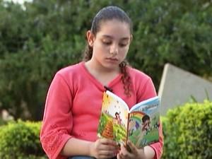 Maria Luiza Amaral observa livro que escreveu (Foto: TV Integração/Reprodução)