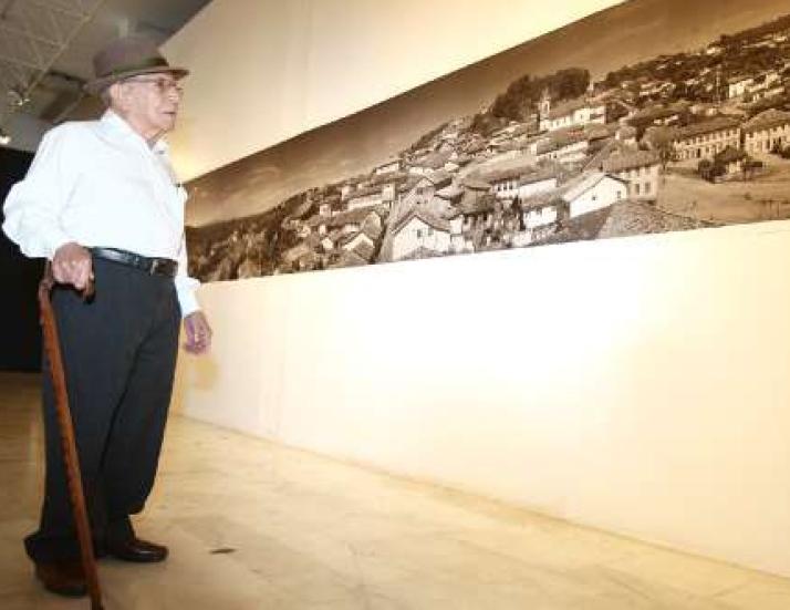 Horta diante de uma de suas 200 fotos em cartaz no Palácio das Artes (Foto: Frederico Haikal / Hoje em Dia)