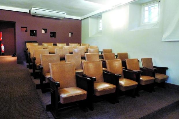 Aconchegante e com clima intimista, sala de projeção tem 25 poltronas estofadas ao estilo modernista (Foto: Reprodução)