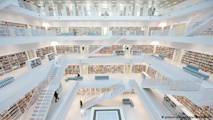 Biblioteca Municipal de Stuttgart. Projetada para ser um centro de produção cultural, a Biblioteca Municipal de Stuttgart foi construída em 2011, como um cubo de nove andares. As paredes externas são de tijolos de vidro levemente acinzentados. No interior, ela é totalmente branca. Os livros que revestem os cinco andares do luminoso vão interno são os únicos arroubos de cor. À noite, a biblioteca é iluminada em diferentes cores (Foto: Reprodução/DW)