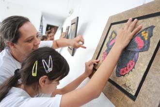 """Crianças entre 6 e 10 anos, do Instituto dos Cegos do Brasil Central, visitaram a exposição """"Borboletas do Cerrado"""", do artista plástico, Ulisses Amaral, na Biblioteca Municipal (Foto: Danilo Cruvinel)"""