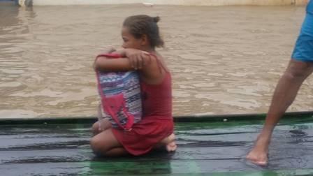 Com a casa inundada, menina é resgatada de jangada (Foto: Válter Rodrigues/Blog Tenório Cavalcanti)